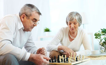 An elderly couple playing a game of chess