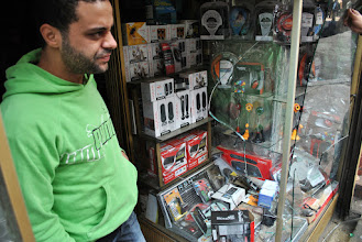 Photo: The patron of an electronics store in downtown Cairo shows media the window-front that was shattered by a tear gas canister fired by police the night before in clashes with protesters