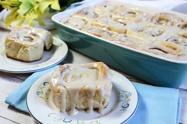 Cinnamon Roll On A Plate With A Tray Of Cinnamon Rolls In The Background.