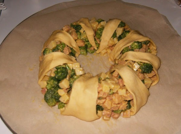 Pull points of roll dough up and over broccoli mixture.