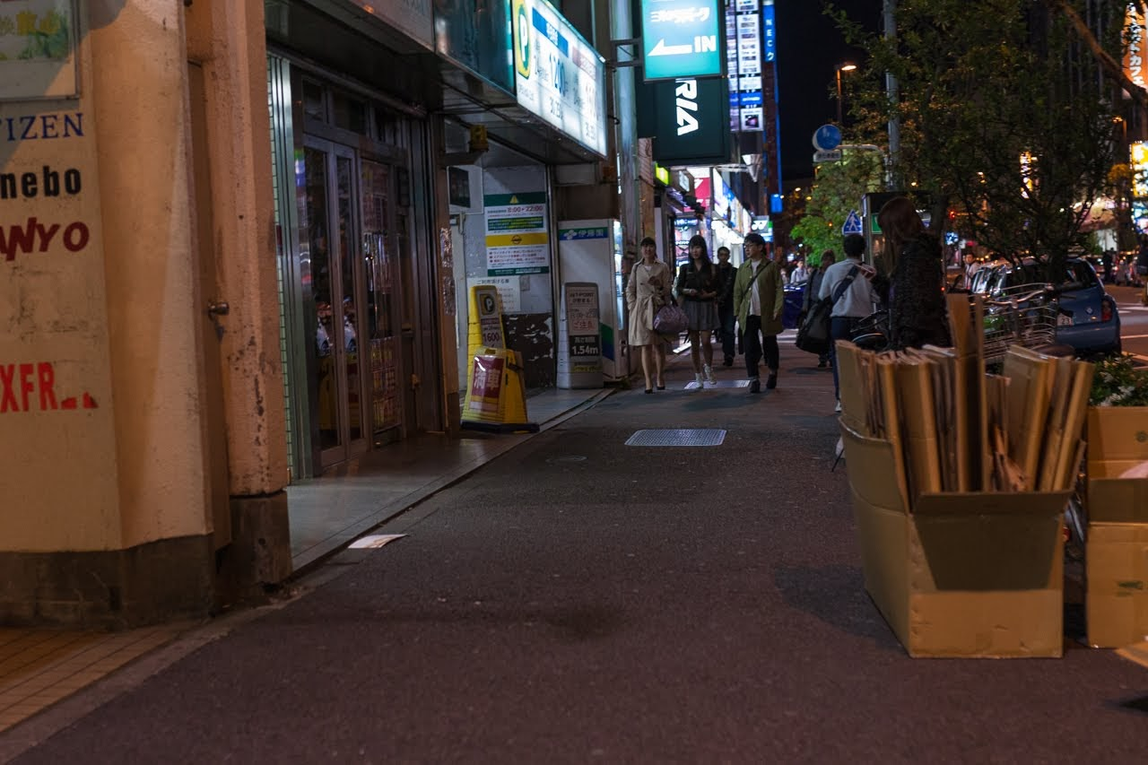 Sidewalk of a few people out in Akihabara at night