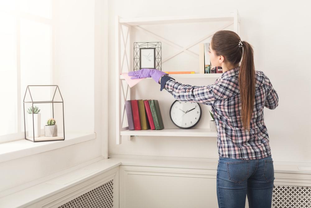 woman dusting shelf