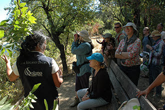 This image shows a Lake Solano Docent leading visitors in a discussion.
