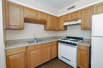D1 kitchen with wood cabinets and white appliances