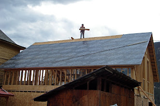 Photo: Loren walking with ease on roof putting down the waterproofing. Powerline across the roof gets changed out soon, but this works for a temporary solution.