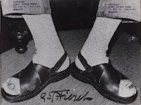 voeten van een zittende man, gestoken in grijze, wollen, sokken en sandalen