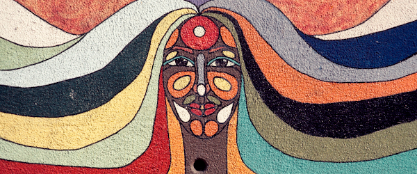Mural on a wall of a woman's face and hair. The mural contains multiple colors on her face and hair.