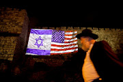A man walks by as the Israeli national flag and an American one are projected on a part of the walls surrounding Jerusalem's Old City December 6, 2017.