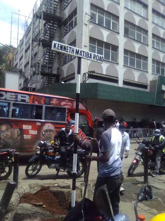 Nairobi government workers erect signpost bearing the new name Kenneth Matiba Road, replacing Accra Road on March 30.