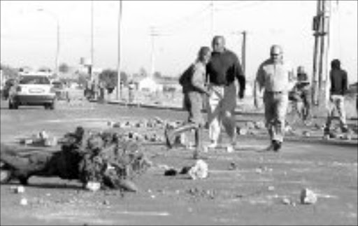 STREET FIGHTING: Residents of Khutsong blocked the access roads to the township with stones. They are protesting their incorporation into North West. Pic. Peter Mogaki. 16/05/2007. 9 Sowetan.