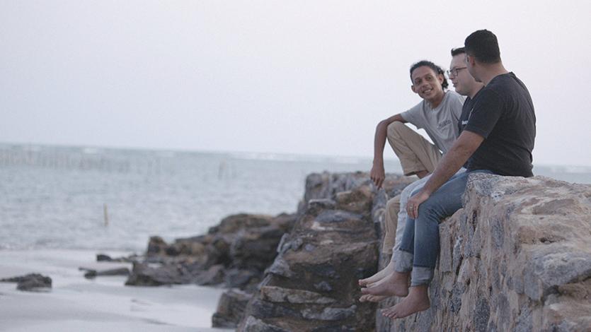 Três homens conversando, sentados em pedras, na praia.