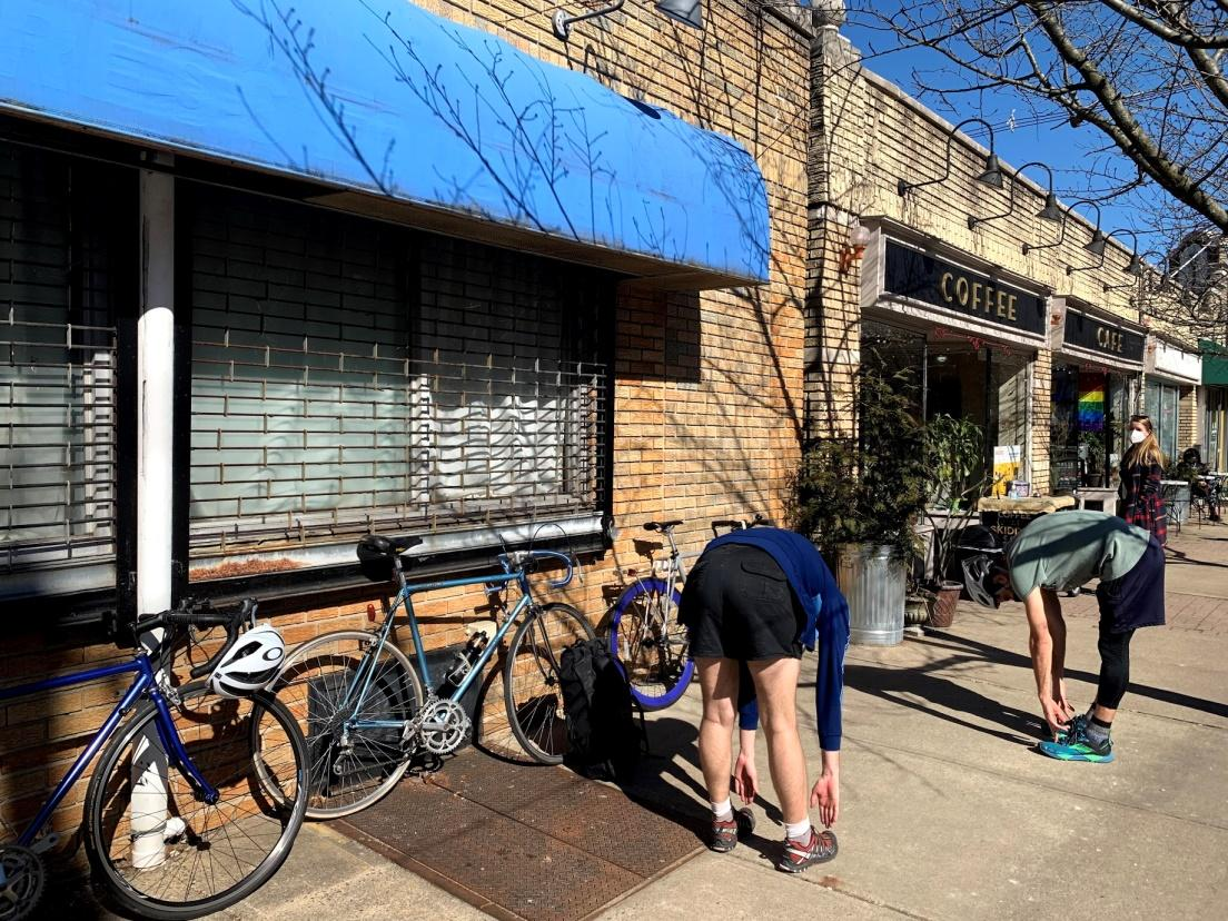 Two people stretch outside a cafe, with three bikes propped up against the wall.
