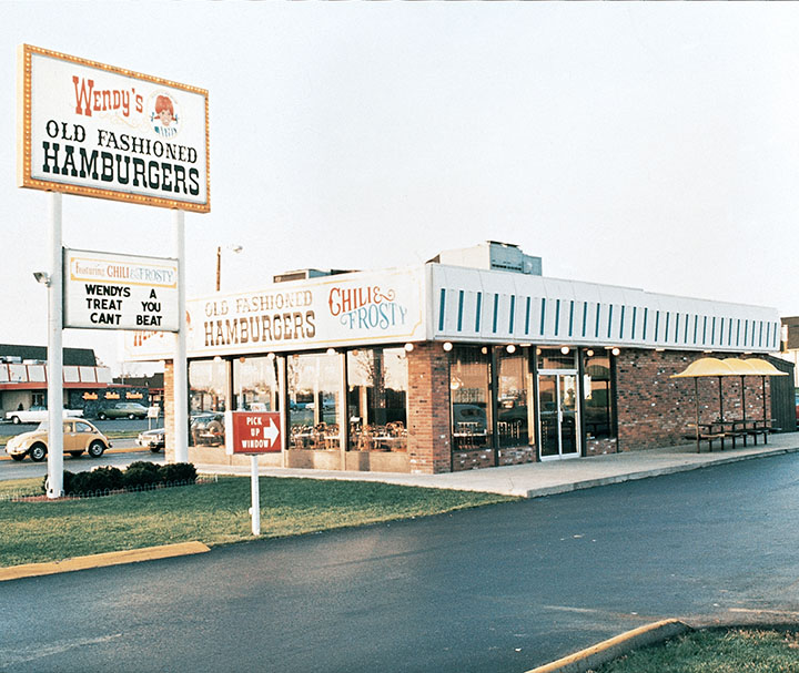 """One of the first Wendy's restaurants with a sign saying """"Wendy's old fashioned hamburgers""""."""