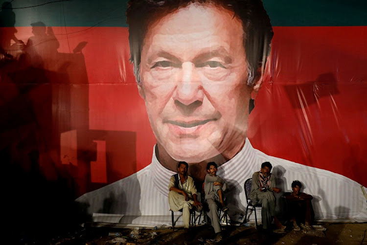 Labourers sit under a billboard displaying a picture of Imran Khan, Pakistan's leader. Picture: REUTERS