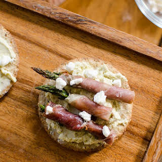Prosciutto Wrapped Asparagus With Goat Cheese On Crackers.