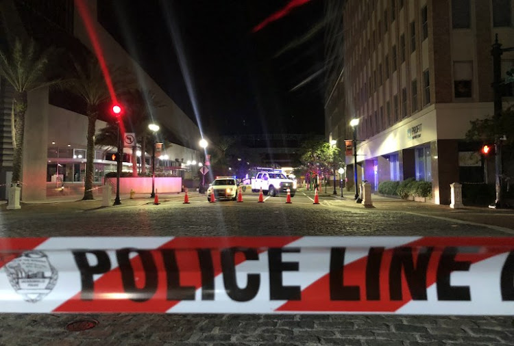 This photo shows a police car behind police tape blocking a street leading to the Jacksonville Landing area in downtown Jacksonville, Florida on August 26 2018, where two people were killed and 11 others wounded.