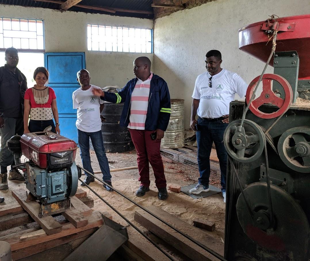 コンゴ民主共和国で、ディーゼル駆動の精米機の周りに集まった 5 人の人々。