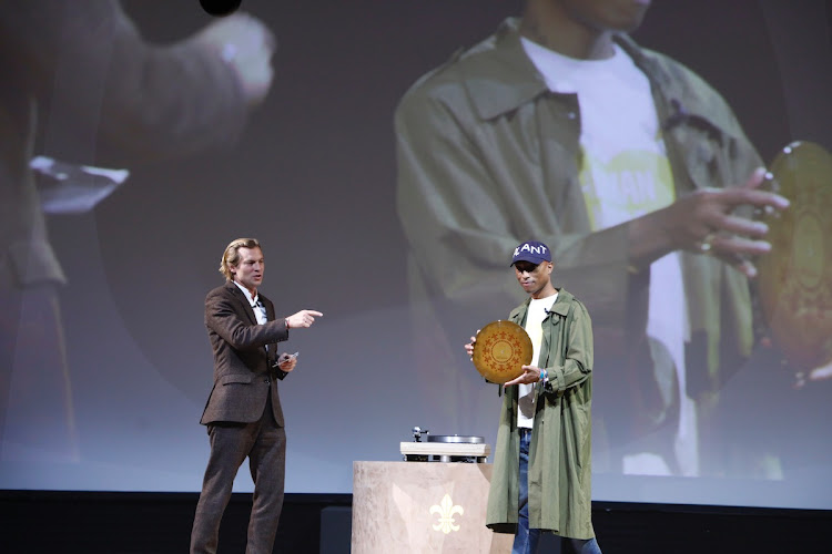 Ludovic du Plessis, global executive director of Louis XIII with Pharrell Williams holding the clay record