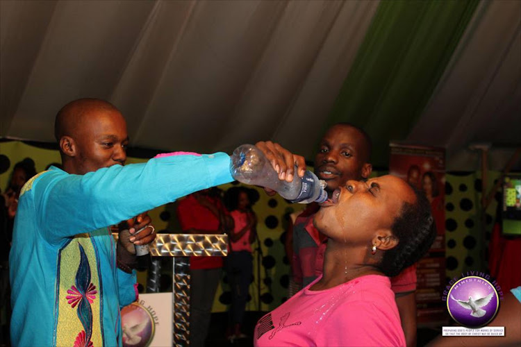 Pastor Light Monyeki feeding a congregant the mixture of water and 'Rattex'. File photo