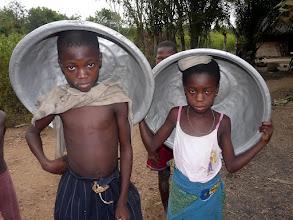 Photo: les bassines ont été remplies d'eau, portées sur la tête, et ramenées au village pour la cuisine et la toilette.