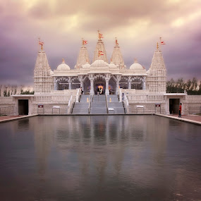 BAPS Shri Swaminarayan Mandir Houston by Winterlyn Stebner - Buildings & Architecture Places of Worship ( clouds, water, wind, building, detail, flags, purple, colorful, carvings, beautiful, art, houston, texas, white, yellow, beauty, architecture, people, photo, worship, sky, blue, sunset, staircase, pond )