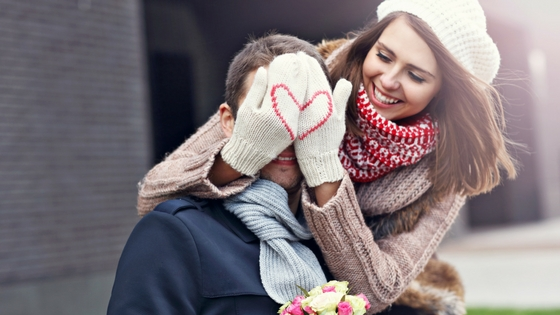 A woman holding mittened hands with a heart stitched into them over a man's eyes; both of them are wearing scarves.