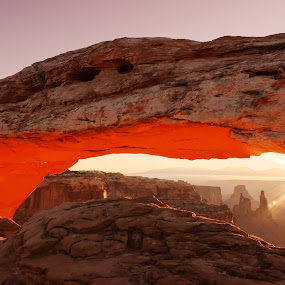 Sunrise at Mesa Arch by Ira Ivanova - Travel Locations Landmarks ( illuminated, pwclandmarks, arch, stone, rock, travel, glow, attraction, geology, sky, nature, mesa, moab, orange, national, canyon, tourism, landmark, tourist, dawn, window, outdoors, western, day, view, natural, west, famous, america, erosion, states, sandstone, beauty, north, landscape, usa, sun, island, southwest, geological, formation, united, desert, park, scenic, morning, red, utah, canyonlands, glowing, sunrise )