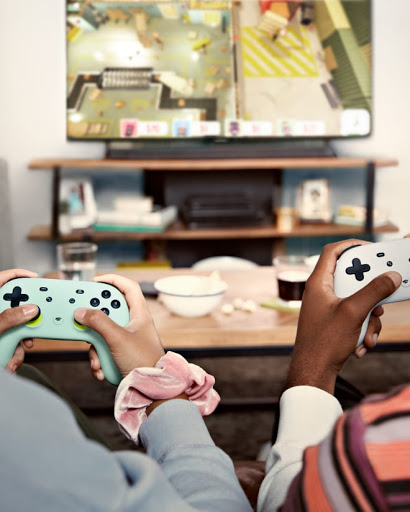 A behind the head shot of two people gaming on their TV and using Stadia controllers.