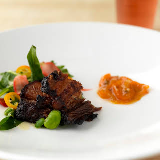 Citrus Brown Sugar-Cured Pork Belly with Kumquat Compote, Dandelion Greens and Fava Beans.