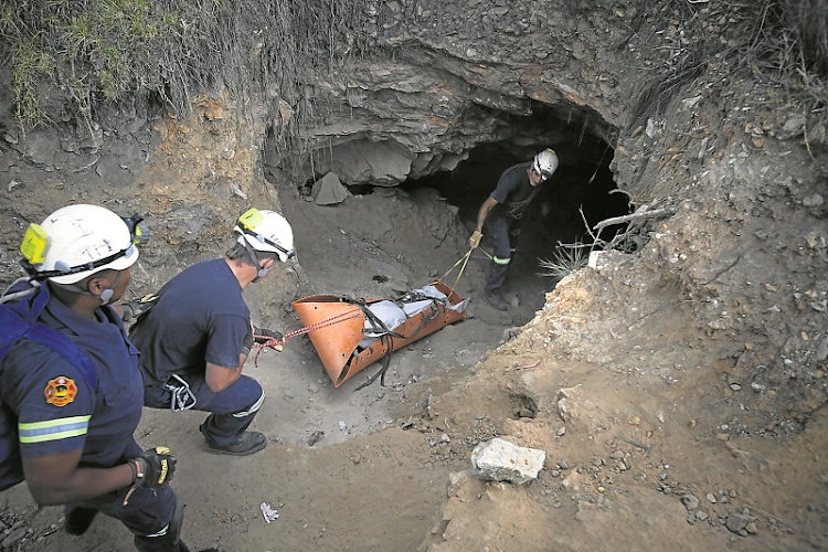 Emergency workers enter the disused Durban Roodepoort Deep mine to retrieve the bodies of illegal miners who died after inhaling underground gases.  Picture: THE TIMES