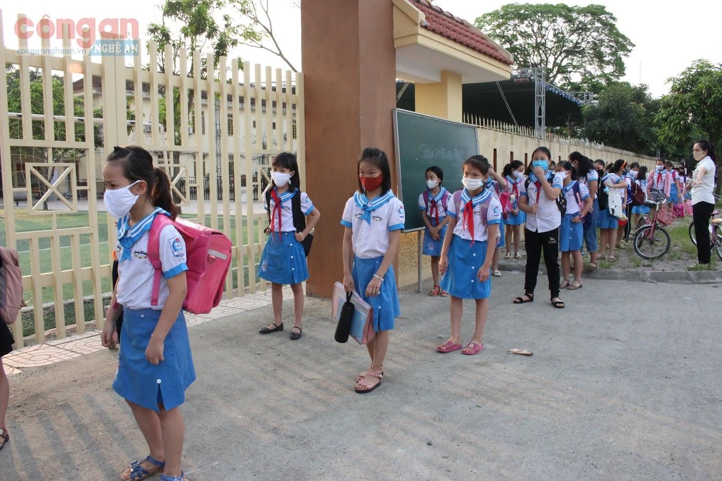 Việc tổ chức giãn cách từ ngoài cổng trước khi vào lớp được trường Tiểu học Lê Lợi, TP Vinh triển khai đầu giờ
