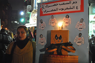 Photo: A woman holds up a sign commemorating the lives of the martyrs who died during the ongoing Egyptian revolution, including the recently slain Mina Daniel at the top-right.