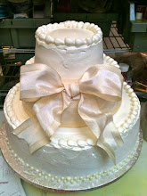 Photo: Elegant Wedding Cake: 3-tiers iced in ivory, Italian whipped cream. Design inspired by bride's wedding gown, featuring a large Ivory bow in front with edible pearl beading on bottom tier.