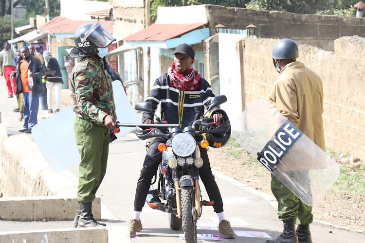 Riot police stop a boda boda rider after fighting broke out during the London by- election on Thursday.