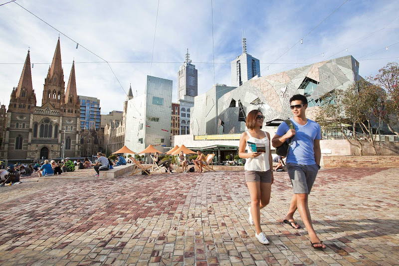 A couple walks through Federation Square in Melbourne, Australia.