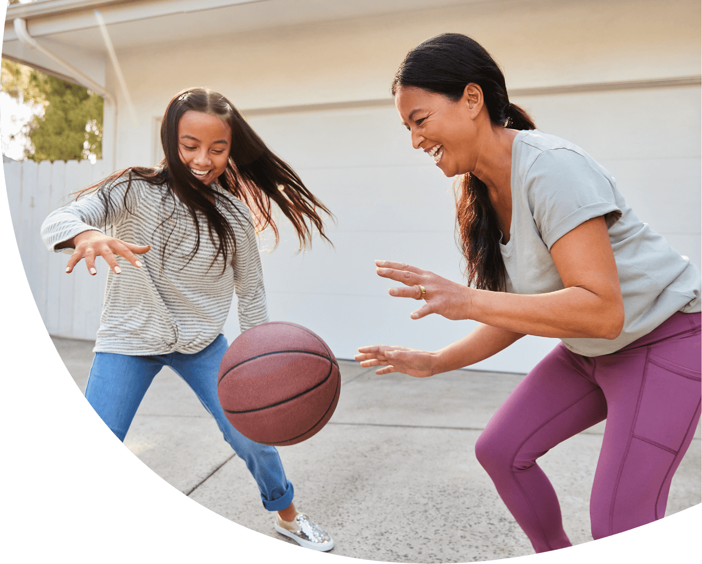Daughter and mother playing basketball