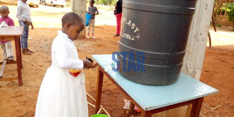 Blessing Mbuvi, a Sunday school girl washes hands outside Africa Inland Church (AIC) in Voi, Taita Taveta County before a church service on Sunday, March 15,2020/SOLOMON MUINGI