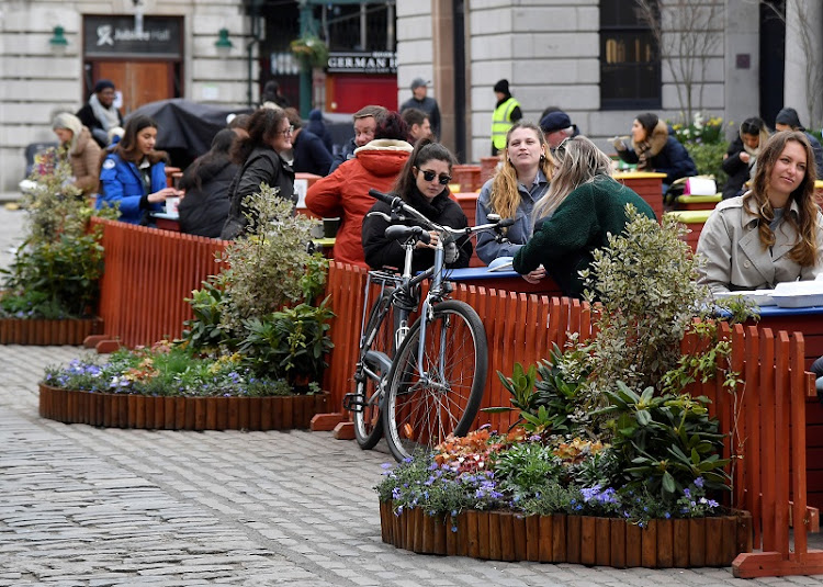 People socialise in a socially distanced outdoor seating area in Covent Garden, London, on April 6 before a further easing of lockdown restrictions for England on April 12.