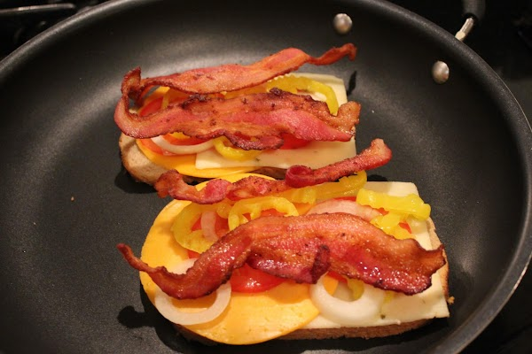Place cheeses on the bread, the cooked bacon, onion, and peppers. Place other slice...