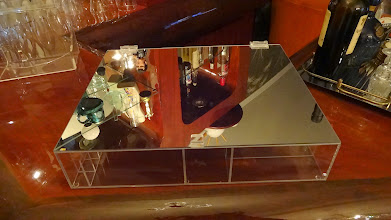 Photo: Caixa modelo A-03. Base em acrílico cristal, Tampa reta em acrílico espelhado. Dimensões: 40 cm de comprimento x 30 cm de largura x 8 cm de altura. Possui 11 nichos para batons e 7 divisórias tamanhos variados.   Nas compras acima de R$150: parcele em até 3 x sem juros no Pag Seguro. Consulte valor com desconto para depósito a vista!   Solte sua imaginação: esta peça é somente referência e pode ser totalmente personalizada para você! *valores sofrem alterações, faça seu orçamento: Acrilico.LB@Gmail.com*