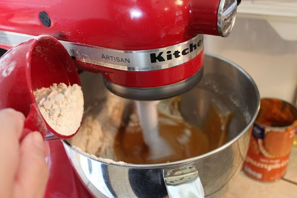 Then using a measuring cup or large spoon, slowly add in scoops of dry...
