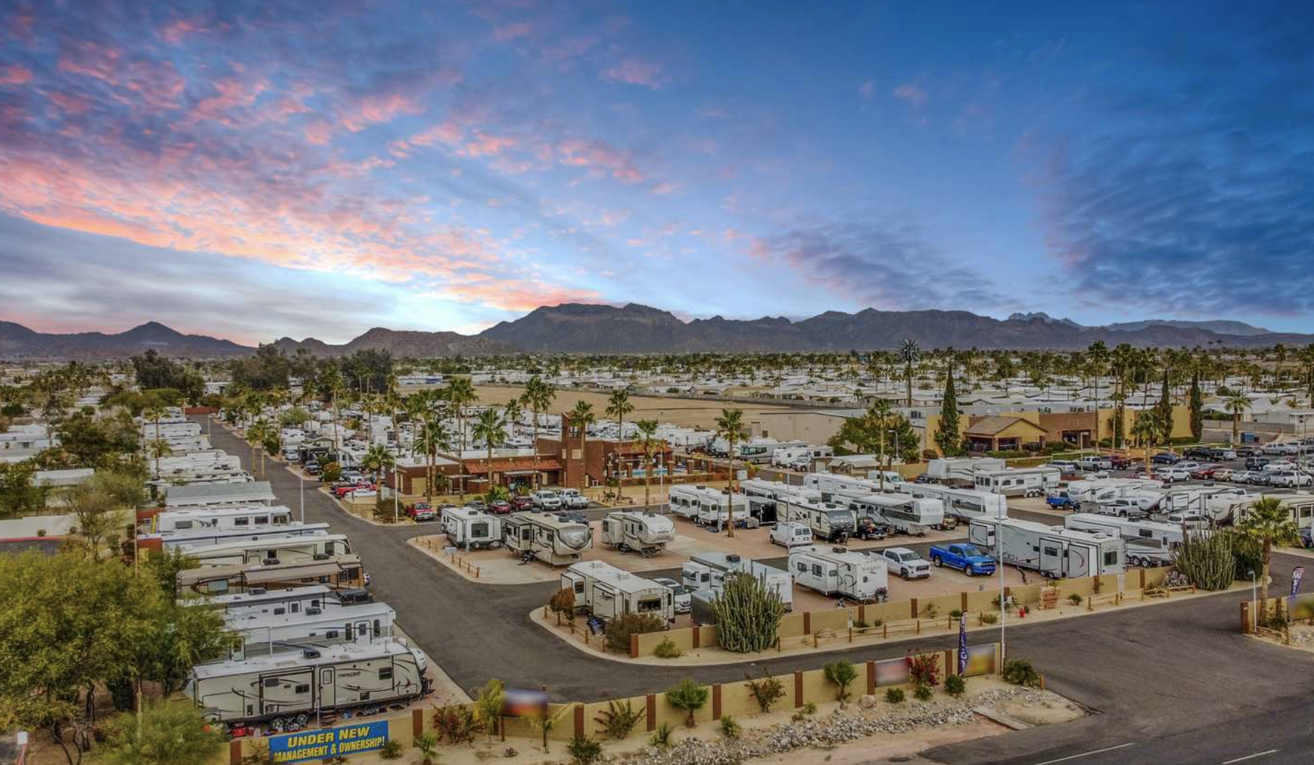 Colorful sunset at RV park with RVs and palm trees - mountains in the distance