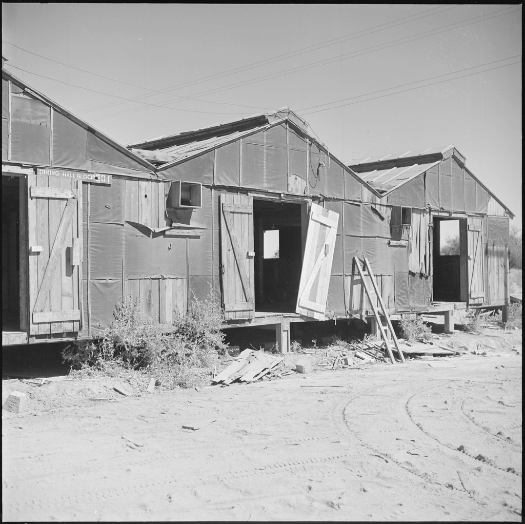 Recently vacated barracks in Manzanar in 1945. The buildings are in decrepit condition, with doors falling off their hinges and tar paper peeling off the walls.