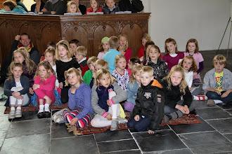Photo: De kinderen gaan op een plek zitten waar ze het Paasspel goed kunnen zien. Het Paasspel gaat over Petrus, één van de leerlingen van Jezus.
