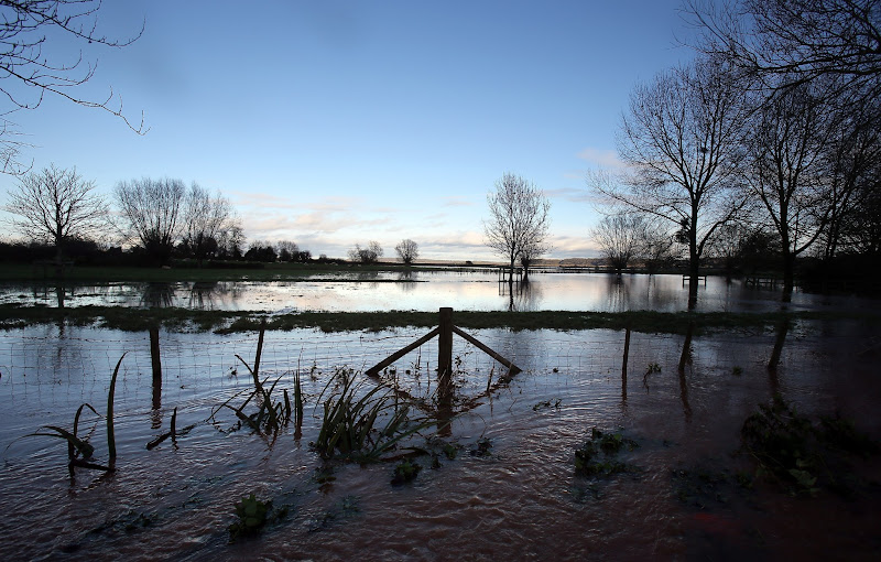Photo: TAUNTON, ENGLAND - NOVEMBER 21:  The sun reflects on the water in flooded fields and roads close to the village of North Curry on November 21, 2012 near Taunton, England. Heavy rain overnight has brought widespread disruption to many parts of the UK particularly in the Somerset and Wiltshire and weather forecasters have warned of more wet and windy weather to come.  (Photo by Matt Cardy/Getty Images)