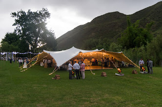 Photo: Getting cosy under the freeform tent on the wedding meadow