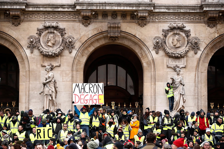 "Protesters wearing yellow vests gather in front of the Opera House as part of the ""yellow vests"" movement in Paris, France, December 15, 2018. Sign reads, ""Macron Get Out"". Picture: REUTERS/CHRISTIAN HARTMANN"
