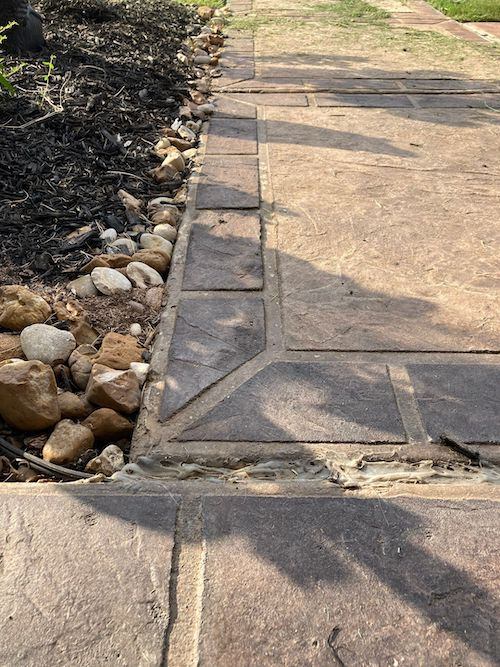 A close up of a sidewalk with stamped concrete detailing that looks like stone. There are small rocks and plants surrounding the sidewalk.