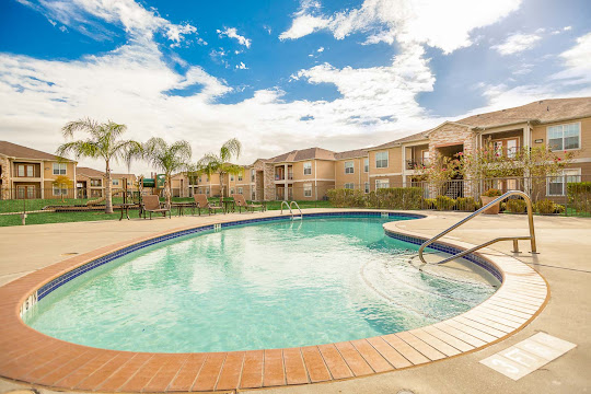 Pool next to apartment buildings with stair access, lounge furniture, and landscaping