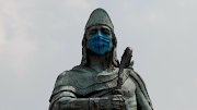 The monument of Tezozomoc is seen with a face mask that reads